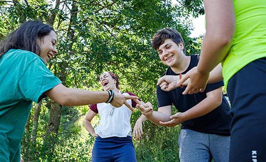 Grup de nens d' Escoltes Catalans jugant a pedra-paper-tisora mentre riuen, a un entorn boscós.